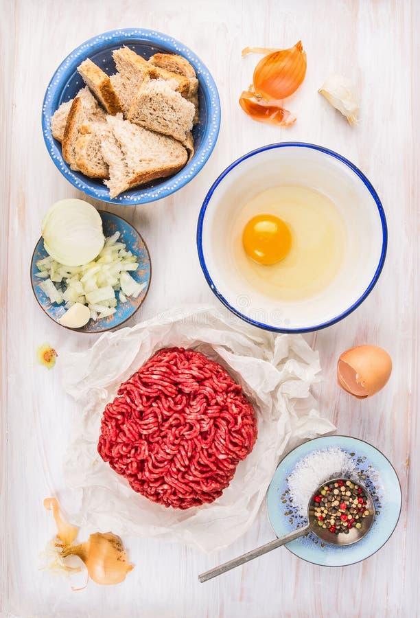 Mięśni pasztecików składniki: minced mięso, surowy jajko, siekająca cebula, czosnek, chleb, sól i pieprz, zdjęcia stock