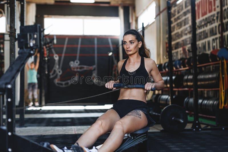 Mięśniowa kobieta używa wioślarską maszynę w sprawność fizyczna klubie obraz stock