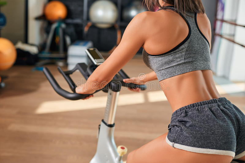 Mięśniowa młoda kobieta pracująca na ćwiczenie rowerze przy gym out obrazy royalty free