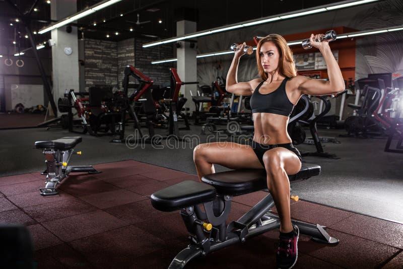 Mięśniowa sprawności fizycznej kobieta robi ćwiczeniom w gym zdjęcie stock