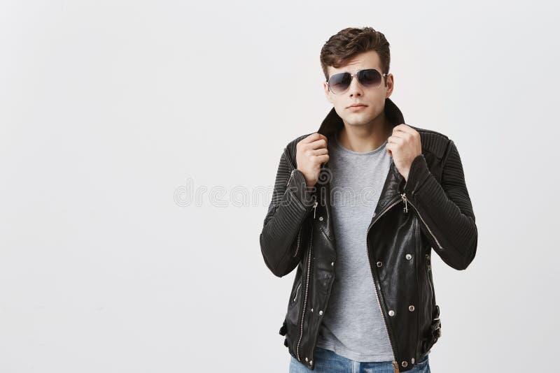Mięśniowa ufna samiec jest ubranym okulary przeciwsłonecznych pozuje indoors Atrakcyjny przystojny facet z modnym ostrzyżeniem w  obraz royalty free