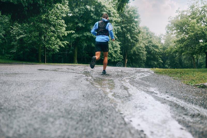 Mięśniowe łydki dysponowany męski jogger szkolenie dla przecinającego kraju lasowego śladu ścigają się w deszczu na natura śladzi obrazy stock