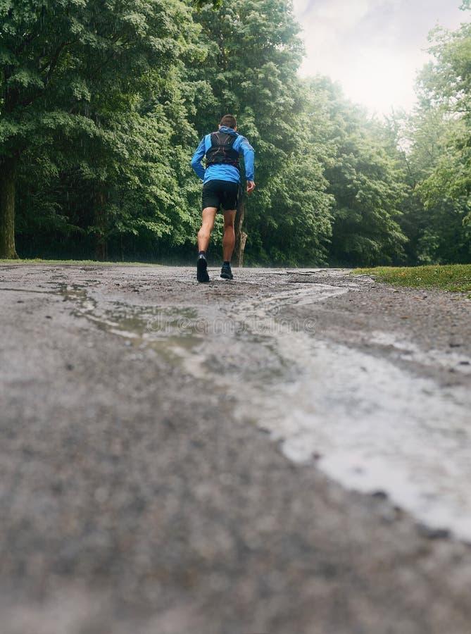 Mięśniowe łydki dysponowany męski jogger szkolenie dla przecinającego kraju lasowego śladu ścigają się w deszczu na natura śladzi zdjęcia stock
