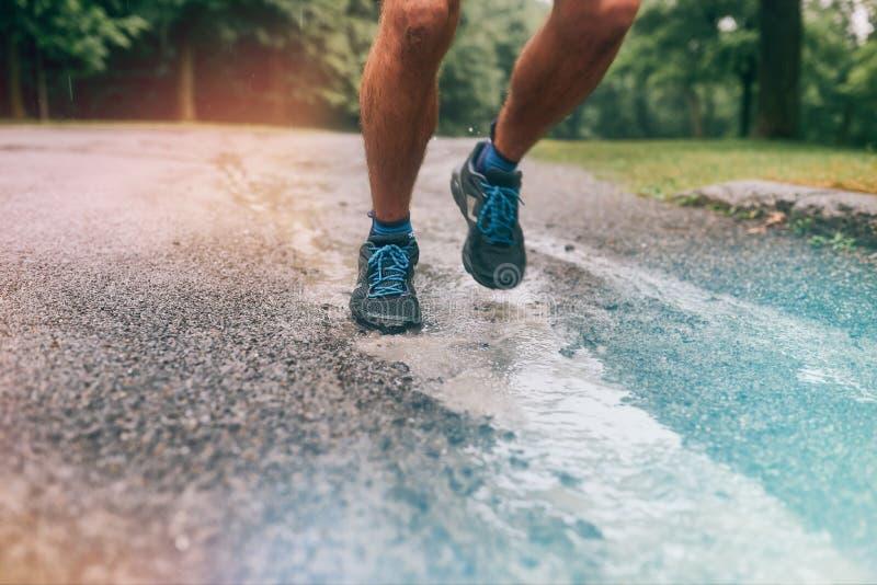 Mięśniowe łydki dysponowany męski jogger szkolenie dla przecinającego kraju lasowego śladu ścigają się w deszczu na natura śladzi zdjęcia royalty free