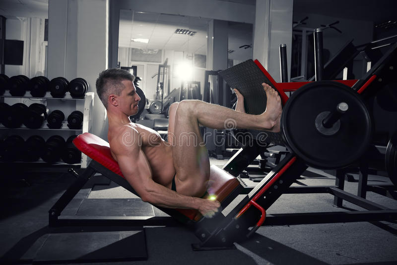 Mięśniowe nogi, przystojny bodybuilder trening na trenerze w gym zdjęcie royalty free