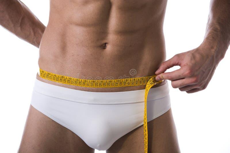 Mięśniowego bez koszuli młodego człowieka pomiarowa talia z taśmy miarą zdjęcie stock