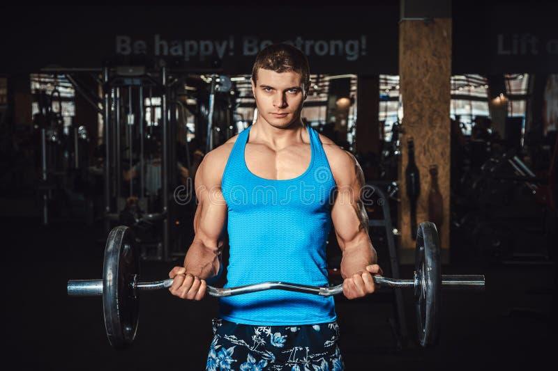 Mięśniowi mężczyzna udźwigu ciężary na bicepsach i spojrzenia przy kamerą zdjęcia royalty free