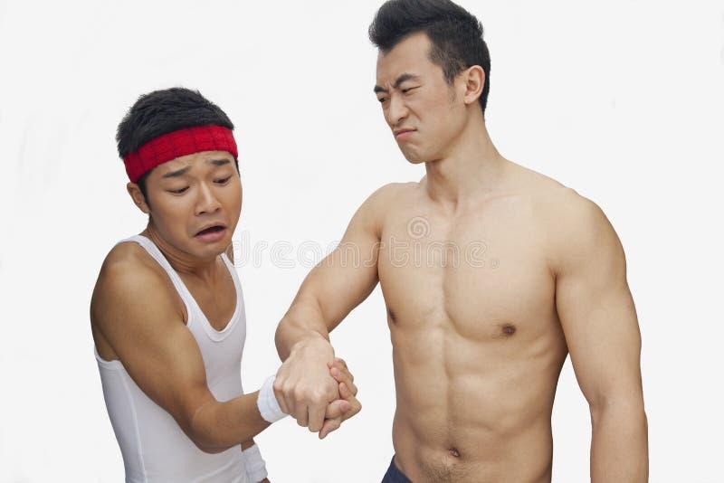 Mięśniowy bez koszuli młody człowiek bije innego młodego człowieka przy ręki zapaśnictwem, studio strzał zdjęcia royalty free