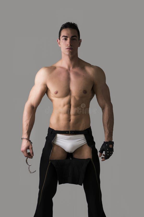 Mięśniowy bez koszuli młody człowiek z kajdankami i nabijającą ćwiekami rękawiczką zdjęcie stock