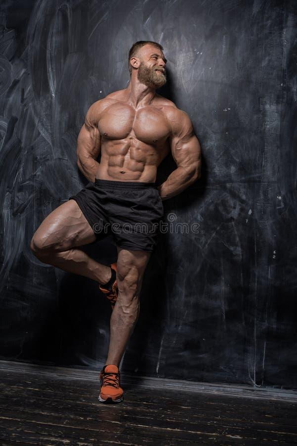 Mięśniowy bodybuilder facet nad ciemnym tłem zdjęcie stock