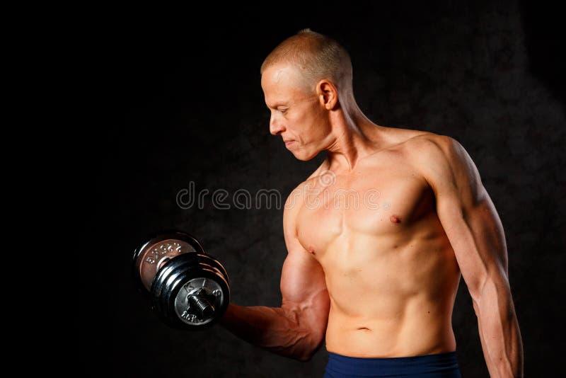 Mięśniowy bodybuilder facet robi ćwiczeniom z dumbbell nad ciemnym tłem zdjęcie stock