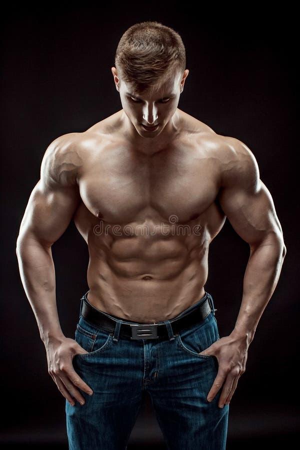 Mięśniowy bodybuilder facet robi pozować nad czarnym tłem fotografia royalty free