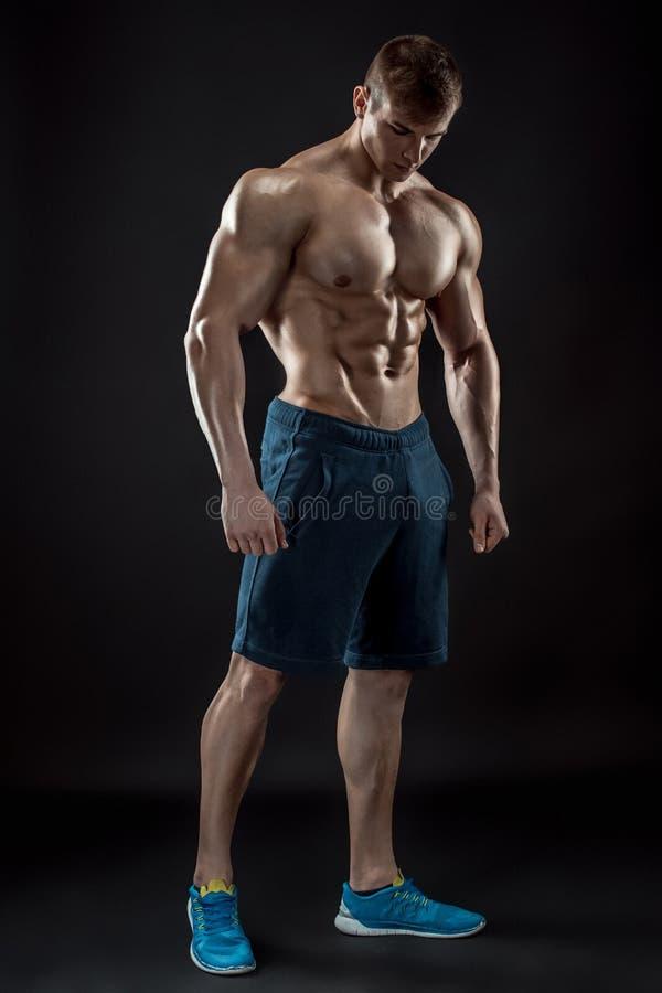 Mięśniowy bodybuilder facet robi pozować nad czarnym tłem obraz stock
