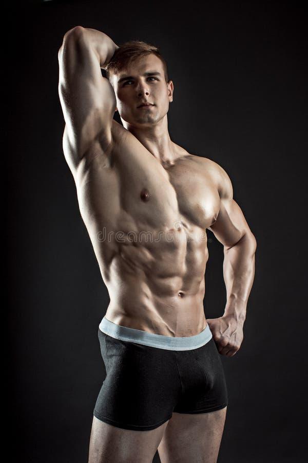 Mięśniowy bodybuilder facet robi pozować nad czarnym tłem zdjęcia royalty free