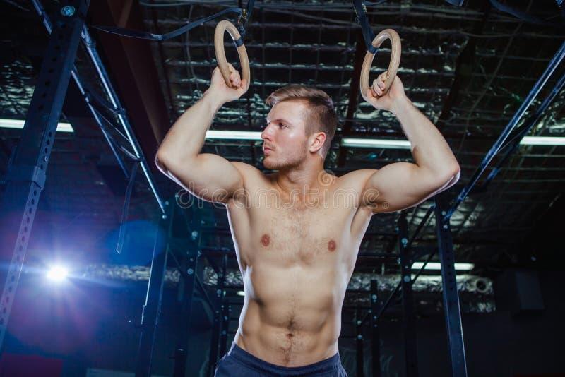 Mięśniowy facet robi ćwiczeniu na pierścionku krzyża napadu stylu zdjęcia royalty free