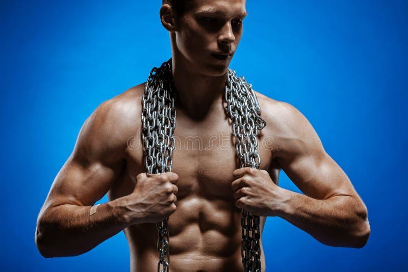 Mięśniowy facet z łańcuchami na jego ramionach przeciw błękitnej ścianie obraz stock