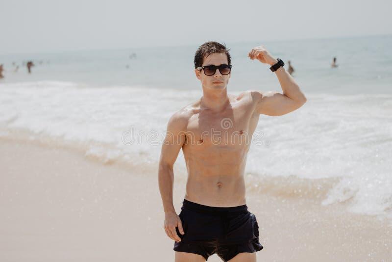 Mięśniowy Hawajski mężczyzna odprowadzenie na plaży jako ocean fala rozbija za on obraz stock