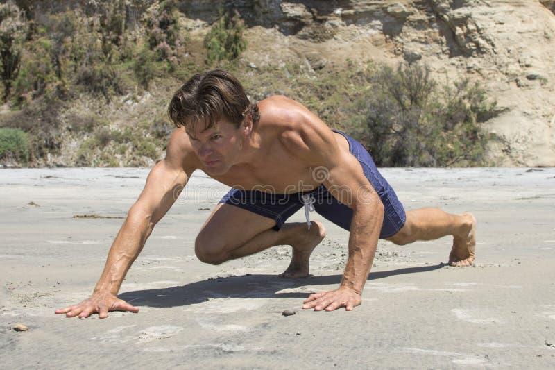 Mięśniowy Kaukaski mężczyzna robi twardemu niedźwiadkowemu kraula treningowi obraz stock