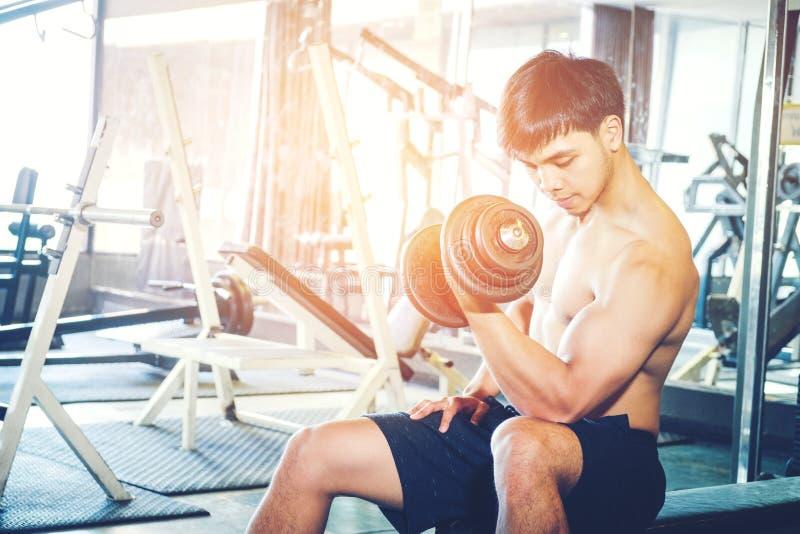 Mięśniowy mężczyzna budował atlety pracującej w gym obsiadaniu na weightl out obrazy royalty free