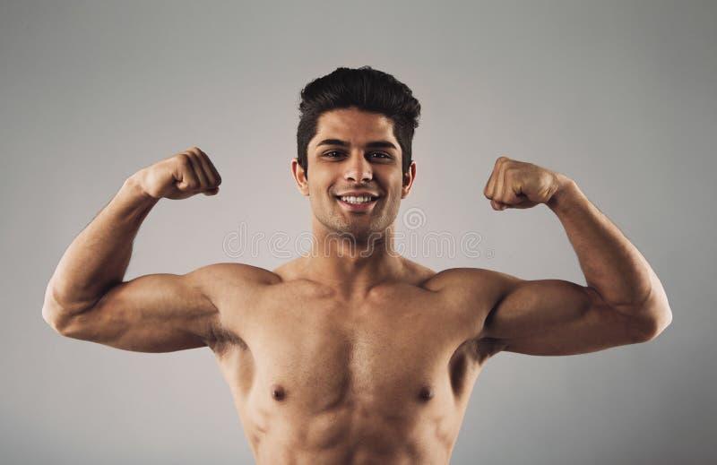 Mięśniowy mężczyzna ciągnie jego bicepsy pokazywać daleko zdjęcie stock