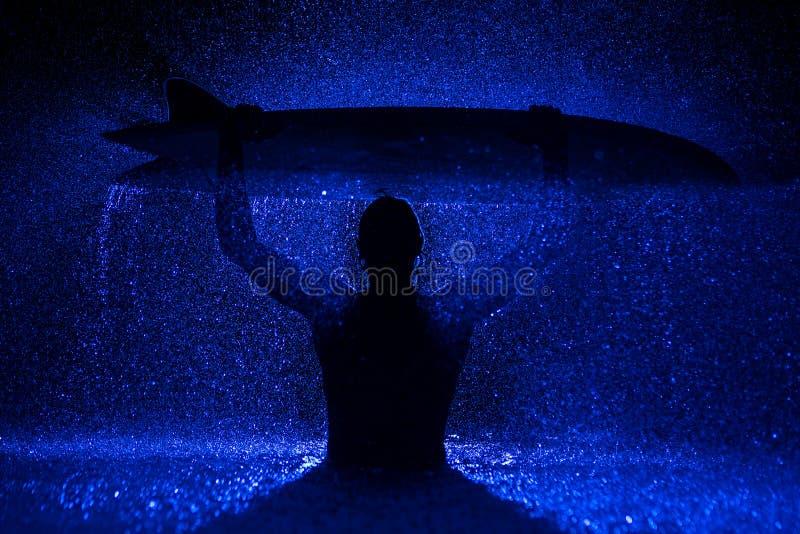 Mięśniowy mężczyzna i surfboard w wodzie fotografia stock