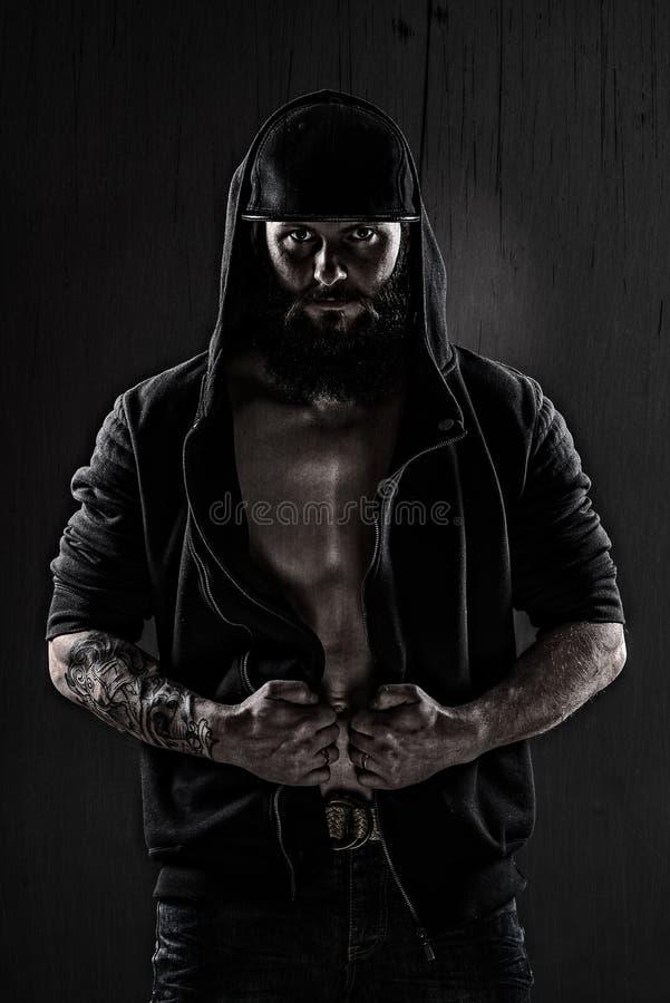 Mięśniowy mężczyzna jest ubranym baseball nakrętkę czarną bluzkę i zdjęcia stock