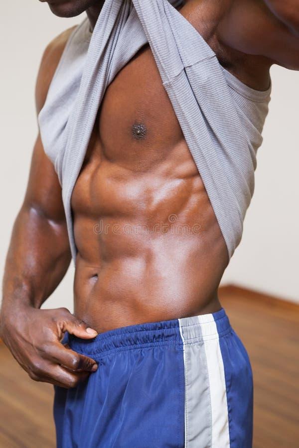Mięśniowy mężczyzna pokazuje jego abs zdjęcie stock