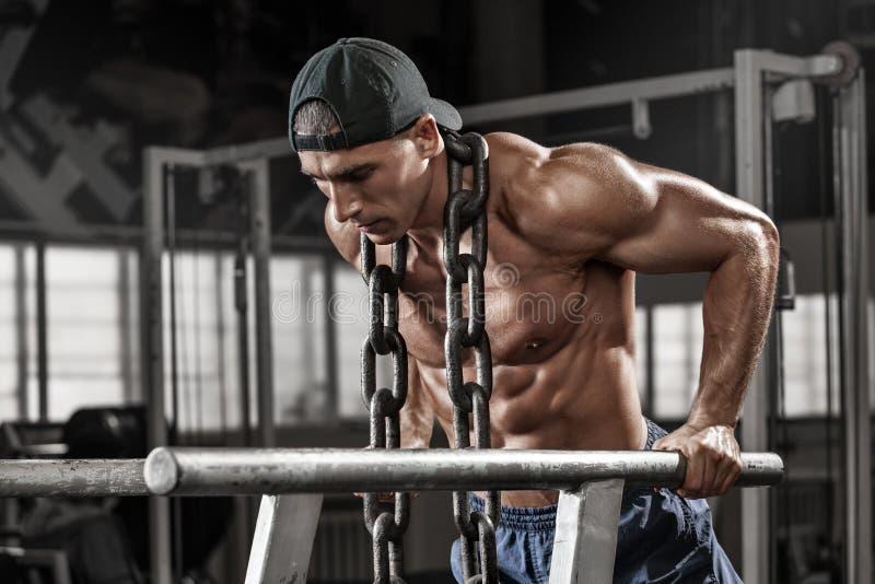 Mięśniowy mężczyzna pracujący w gym robi ćwiczeniom na równoległych barach z łańcuchem out, silny męski nagi półpostaci abs obraz stock