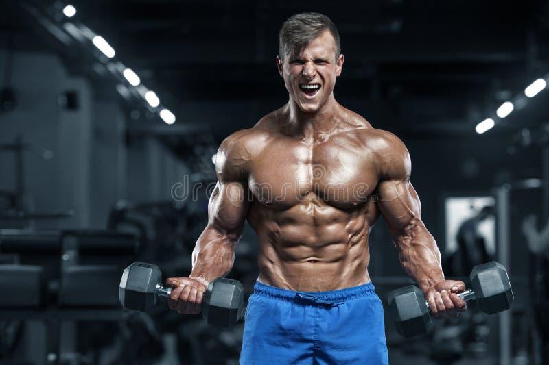 Mięśniowy mężczyzna pracujący w gym robi ćwiczeniom out, silny męski półpostaci abs obraz royalty free