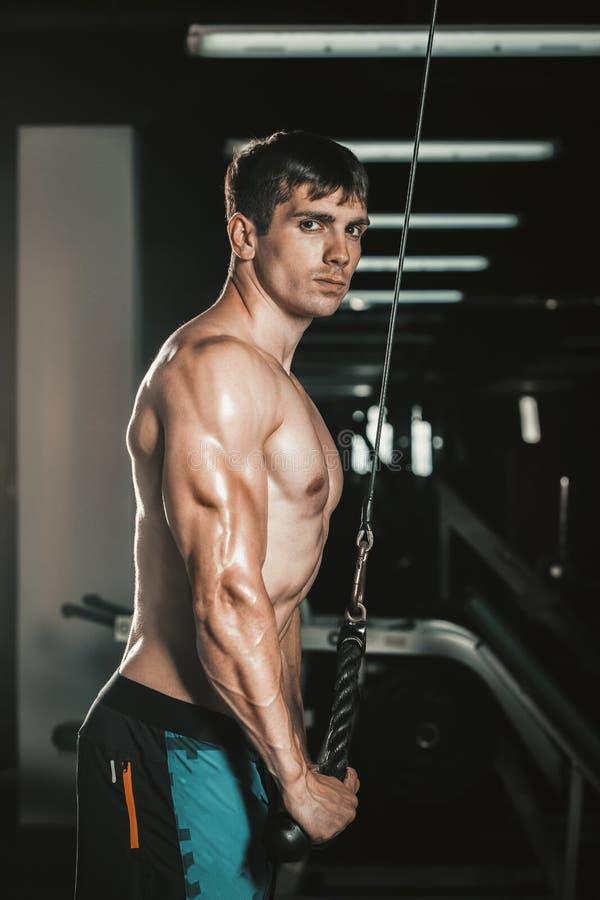 Mięśniowy mężczyzna pracujący w gym robi ćwiczeniom przy triceps out, silny męski nagi półpostaci abs obrazy stock