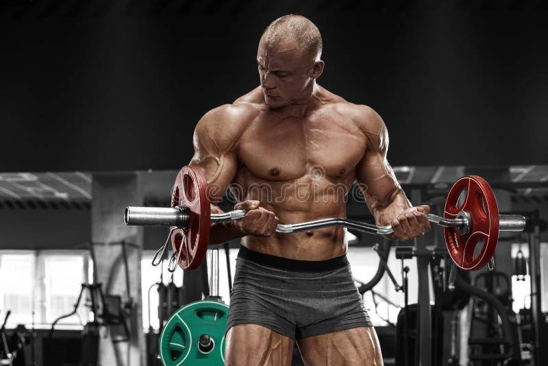 Mięśniowy mężczyzna pracujący w gym robi ćwiczeniom z barbell out, silny męski nagi półpostaci abs fotografia royalty free