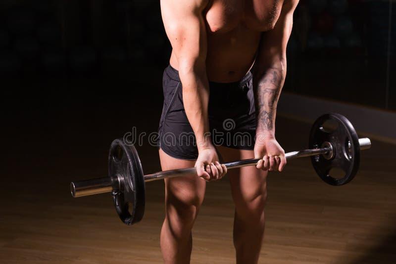 Mięśniowy mężczyzna pracujący w gym robi ćwiczeniom z barbell zakończeniem out, silny męski nagi półpostaci abs zdjęcia stock