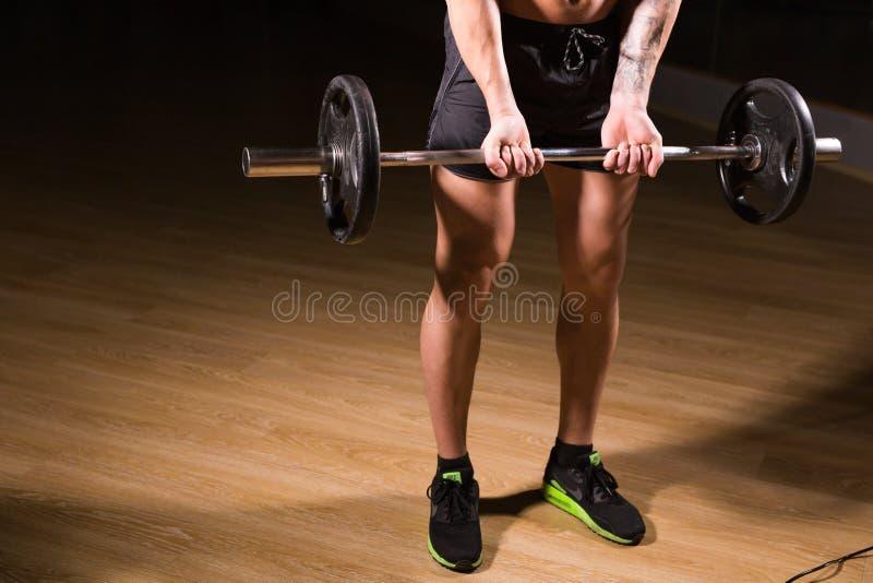 Mięśniowy mężczyzna pracujący w gym robi ćwiczeniom z barbell zakończeniem out, silny męski nagi półpostaci abs zdjęcie royalty free