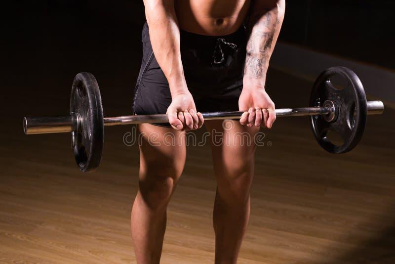 Mięśniowy mężczyzna pracujący w gym robi ćwiczeniom z barbell zakończeniem out, silny męski nagi półpostaci abs obrazy stock