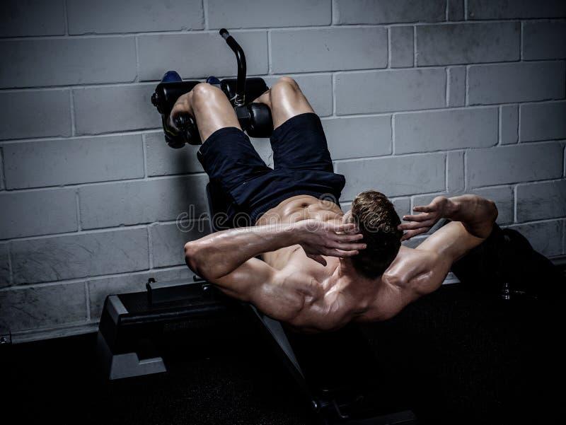 Mięśniowy mężczyzna robi ćwiczeniom dla brzusznego w Gym zdjęcie stock