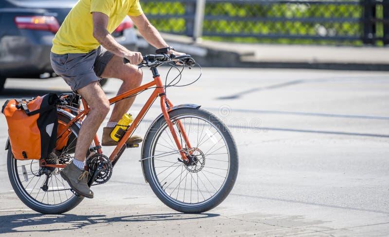 Mięśniowy mężczyzna w koszulce i skrótach woli aktywnego styl życia i jedzie bicykl zdjęcie stock