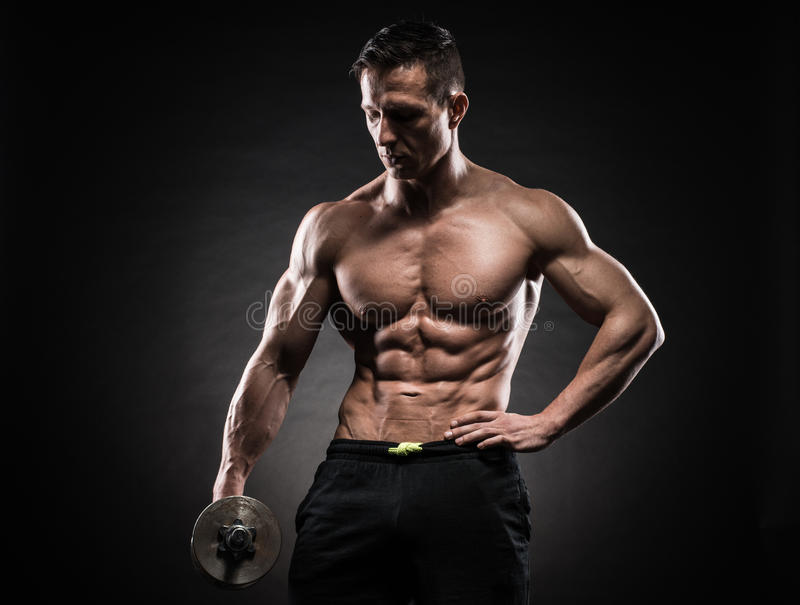 Mięśniowy mężczyzna w studiu na ciemnym tle zdjęcia royalty free