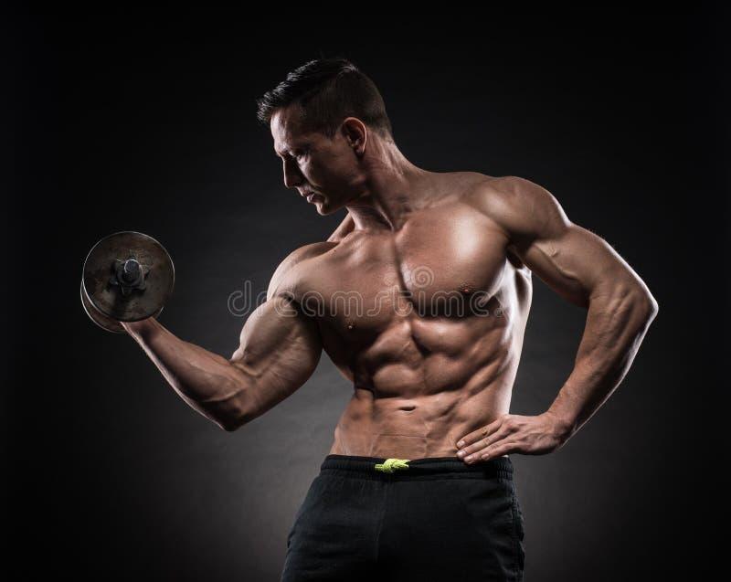 Mięśniowy mężczyzna w studiu na ciemnym tle zdjęcie royalty free