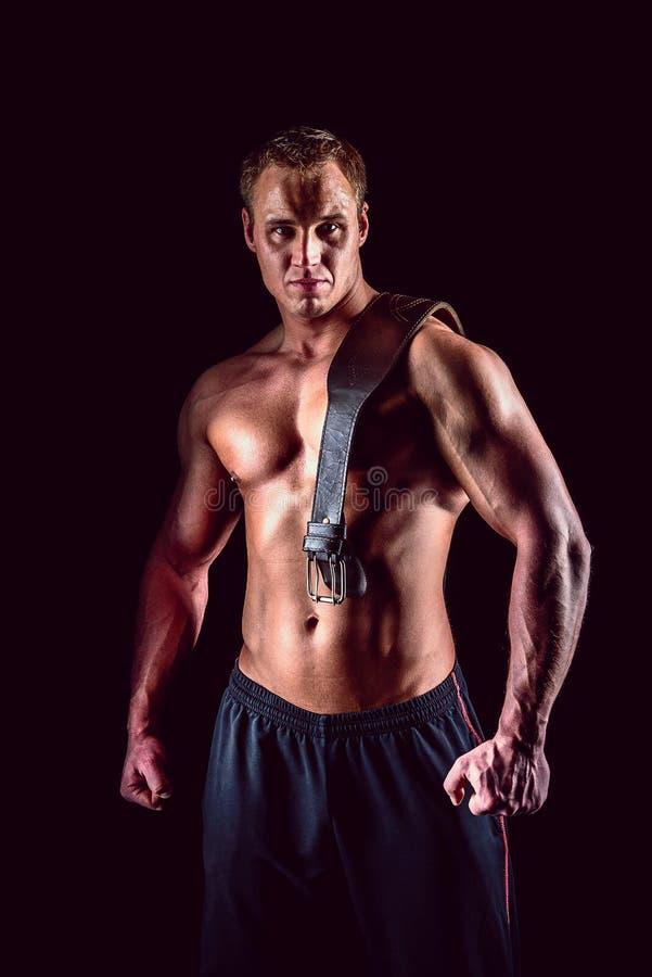 Mięśniowy mężczyzna wewnątrz z udźwigu pasowy pozować nad ciemnym tłem zdjęcie royalty free