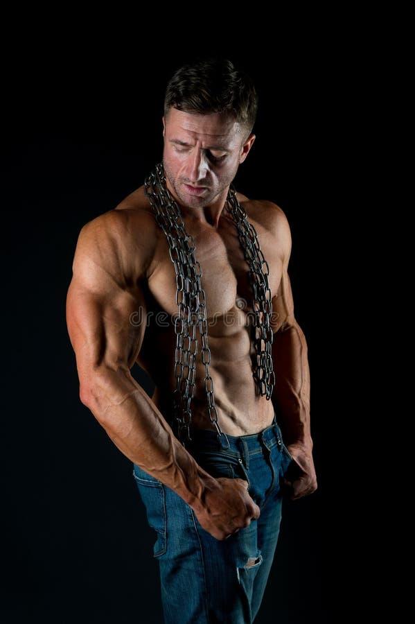 Mięśniowy mężczyzna z łańcuchem na seksownym ciele M??czyzna z seksown? nag? p??postaci? w cajgach Atleta z seksowną nagą półpost fotografia royalty free