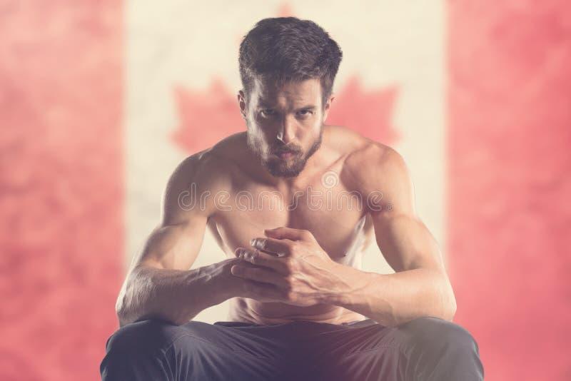 Mięśniowy mężczyzna z kanadyjczyk flaga behind zdjęcie stock
