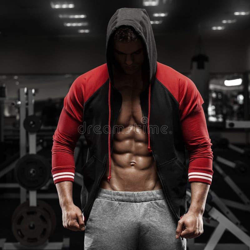 Mięśniowy mężczyzna z otwartej kurtki odkrywczym abs w gym, trening Kształtny brzuszny obraz royalty free