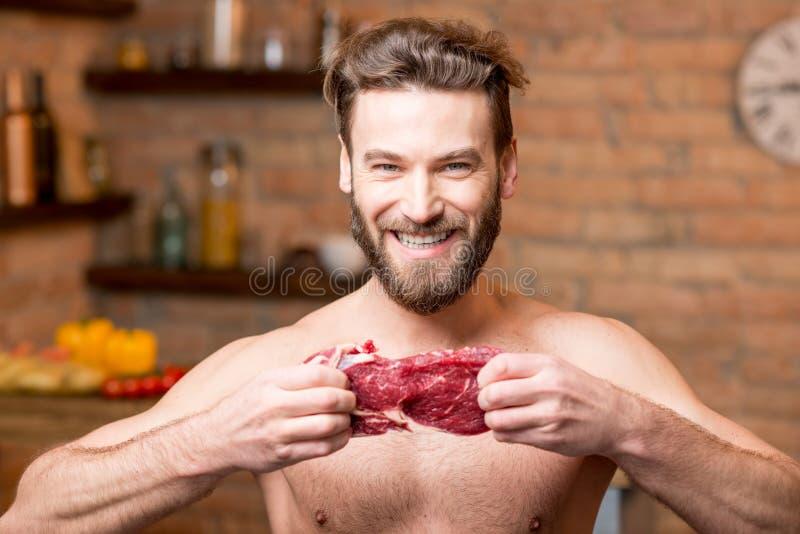 Mięśniowy mężczyzna z surowym mięsem obraz stock