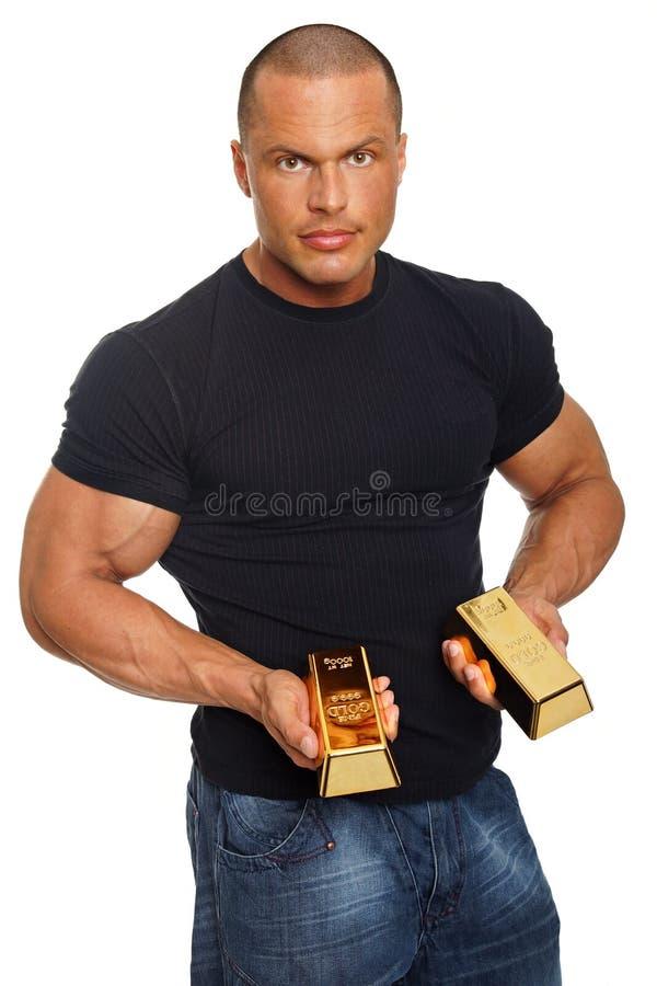 Mięśniowy mężczyzna z złocistą cegłą zdjęcie royalty free