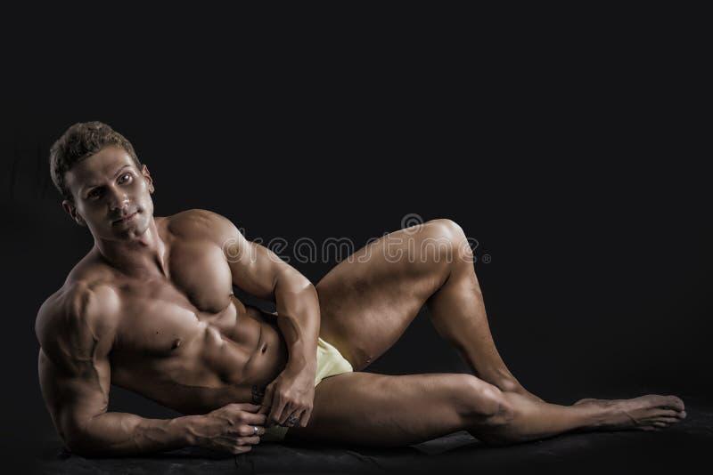 Mięśniowy młody bodybuilder kłaść w dół w zrelaksowanym zdjęcia royalty free