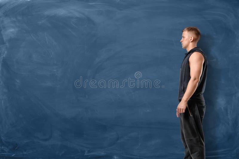 Mięśniowy młody człowiek jest trwanie i patrzejący naprzód na błękitnym chalkboard tle fotografia stock