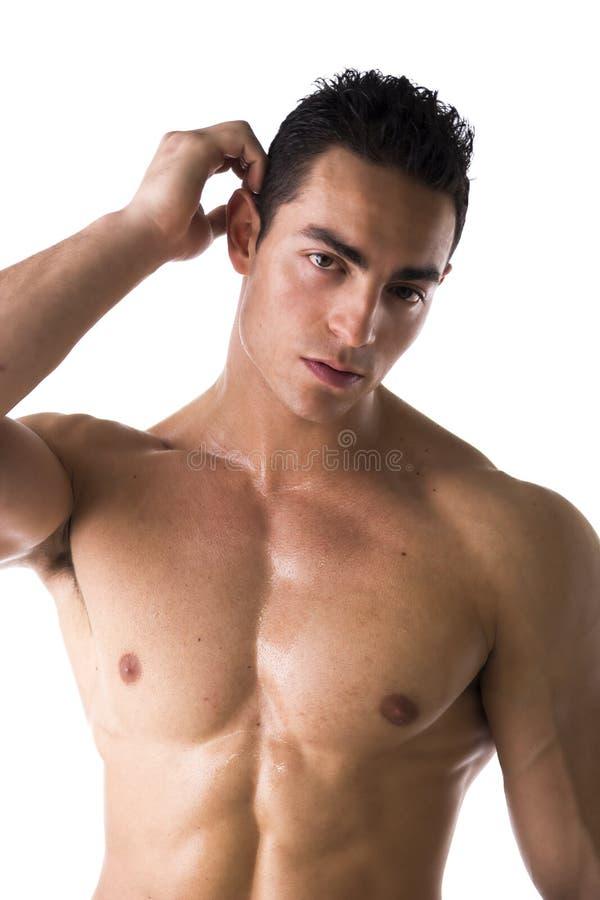 Mięśniowy młody człowiek niepewny lub zmieszany, chrobot głowa fotografia stock