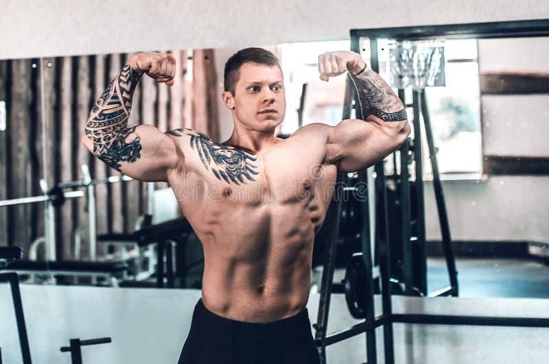 Mięśniowy młody człowiek pozuje w gym zdjęcie royalty free