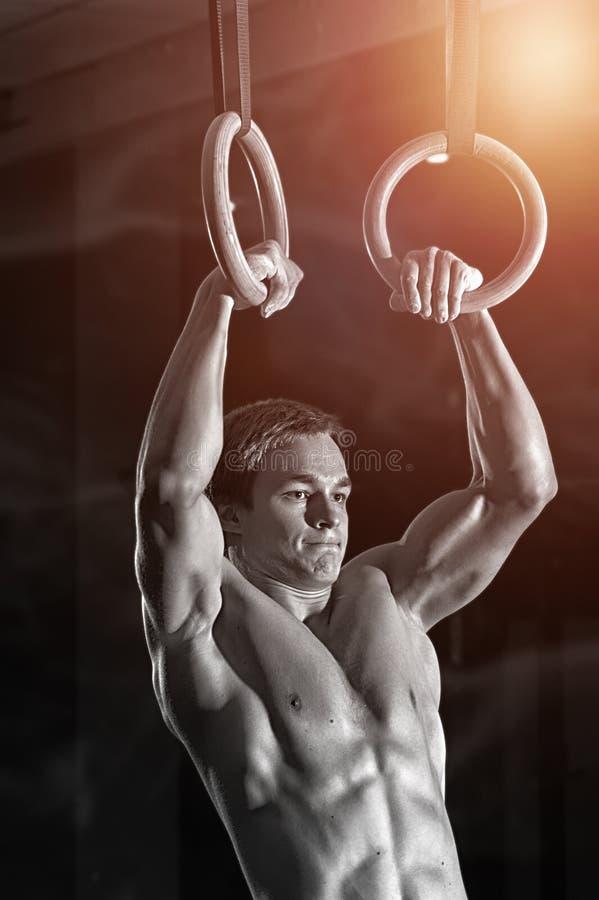Mięśniowy młody człowiek pracujący na gimnastyka pierścionkach out obraz stock