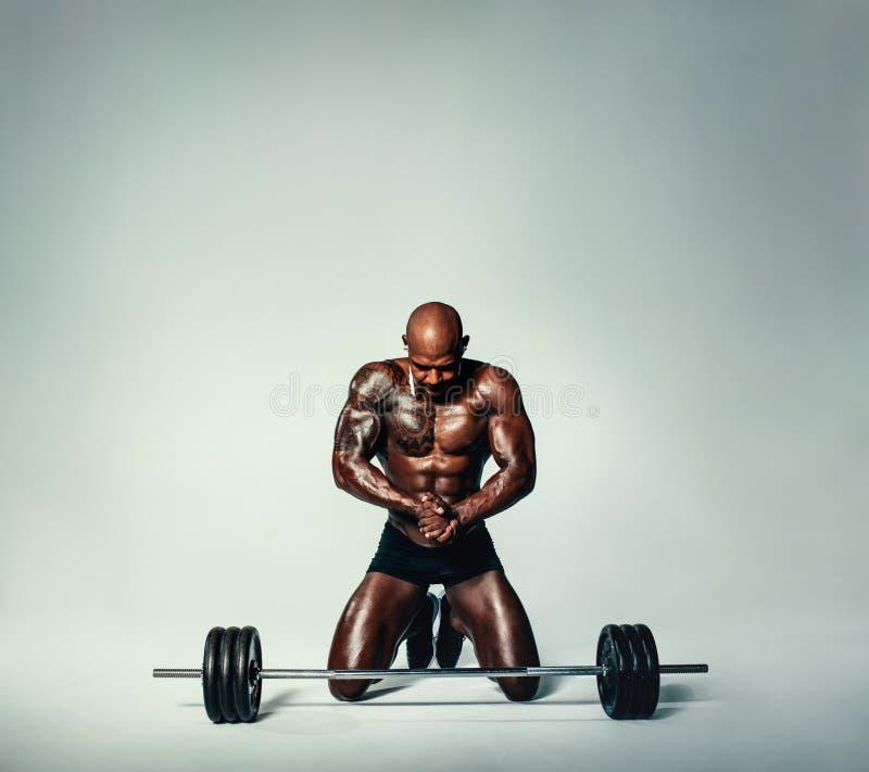 Mięśniowy młody człowiek pracujący z ciężkimi ciężarami out zdjęcie stock